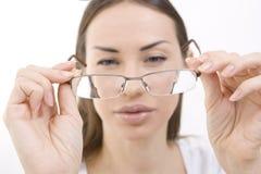 Оптика и стекла, портрет молодой женщины смотря через ее стоковые изображения