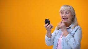 Оптимистическая достигшая возраста дама смотря в зеркале и прикладывая губную помаду датируя для пенсионеров акции видеоматериалы