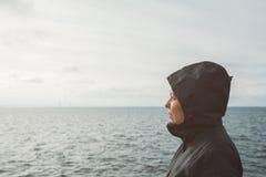 Оптимистическая женская персона наслаждаясь coastl солнечного света утра на море Стоковое Изображение