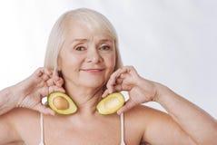 Оптимистическая постаретая женщина имея половины авокадоа в ее руках Стоковые Изображения