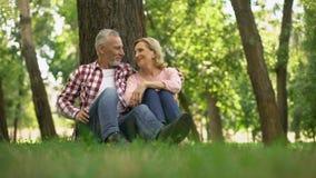 Оптимистические выбытые пары ослабляя на траве в парке, планируя выходные лета видеоматериал