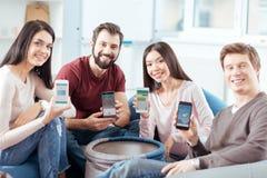 Оптимистические 4 друз показывая их устройства Стоковые Фото