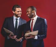 Оптимистические умелые бизнесмены разговаривают с улыбкой стоковые изображения