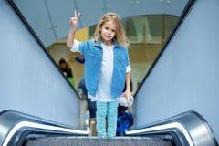Оптимистический стильный ребенок стоит на эскалаторе Стоковые Изображения
