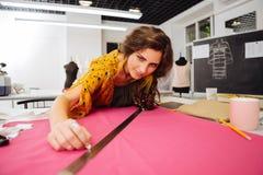 Опытная склонность dressmaker на таблице и смотреть ткань стоковые изображения