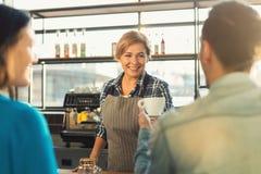 Опытное усмехаясь barista делая кофе к клиентам Стоковая Фотография RF
