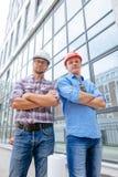 Опытные бизнесмены в вскользь одеждах и защитных шлемах представляя к камере стоковое изображение rf