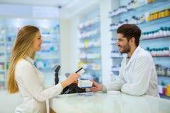 Опытный аптекарь консультируя женский клиент Стоковое Изображение RF