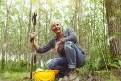 Опытный женский lumberjack пока посещающ лес Стоковые Изображения RF