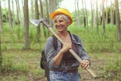 Опытный женский lumberjack пока посещающ лес Стоковое Изображение RF
