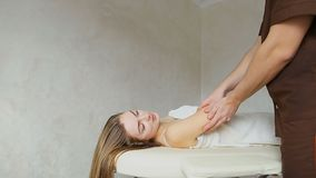 Опытный медицинский мужской специалист с нежными движениями вручает массаж для девушки к пациенту, который лежит на кресле внутри акции видеоматериалы
