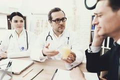 Опытный невропатолог дает стекло взрослого мужчины выпивать с смесью головных болей Стоковые Изображения