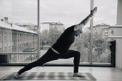 Опытный человек йоги делая различные представления внутри помещения, панорамный вид на город на предпосылке Стоковые Изображения RF