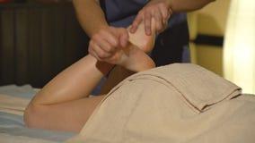 Опытный masseur делая массаж икры ` s молодой женщины сток-видео