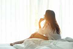 Опять женщина ослабляет в кровати стоковое фото rf