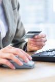 Оплата бизнесмена с ее кредитной карточкой на интернете Стоковое фото RF
