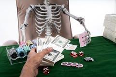 Оплата под рукой селективного фокуса держит пари к скелету картежника на казино t Стоковые Фотографии RF