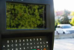 Оплата штрафа за нарушение правил стоянки подвергает автопарковочный счетчик механической обработке стоковые фото