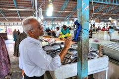 Оплата для приобретений на базаре рыб используя передвижной стержень, Иран Стоковое Изображение