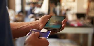 Оплата App кредитной карточки прикрепленная к мобильному телефону стоковое изображение