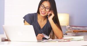 Оплаты японской женщины подтверждая над телефоном стоковые фото