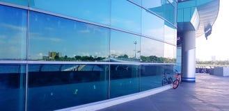 Оранжевая автостоянка велосипеда на стороне здания сделанного из стекла с отражением от голубого неба и белых облаков с spac экзе стоковая фотография