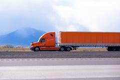 Оранжевая большая снаряжения тележка semi при длинный semi трейлер бежать на Стоковая Фотография RF