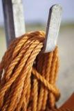 Оранжевая веревочка безопасности нейлона свернулась спиралью на крюке металла Стоковое Фото