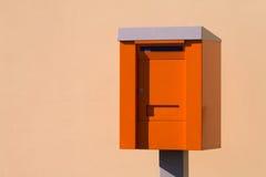 Оранжевая коробка столба mailbox изолированный над светлой предпосылкой Стоковая Фотография