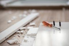Оранжевая отвертка лежа на деревянном элементе новой мебели Стоковое фото RF