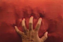 Оранжевая рука маникюра хватая оранжевую подушку - соответствуя цвета стоковые изображения rf