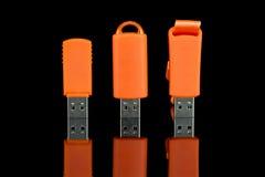 Оранжевая ручка вспышки USB на черной предпосылке Стоковое фото RF