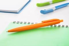 Оранжевая ручка шарика plastik с зеленой тетрадью Стоковое фото RF