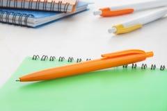Оранжевая ручка шарика plastik с зеленой тетрадью Стоковые Фото
