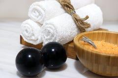Оранжевая соль для принятия ванны в деревянном шаре и 3 белых полотенца на деревянной стойке и камнях Bian черноты стоят на белой Стоковое Изображение