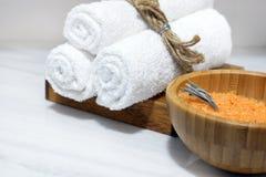 Оранжевая соль для принятия ванны в деревянном шаре и 3 белых полотенца на деревянной стойке стоят на белой мраморной таблице Стоковые Фотографии RF