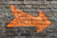 Оранжевая стрелка на стене Стоковая Фотография RF