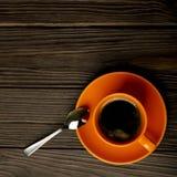 Оранжевая чашка кофе на темной деревянной предпосылке Стоковые Изображения
