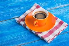 Оранжевая чашка кофе с салфеткой Стоковая Фотография RF
