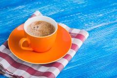 Оранжевая чашка кофе с салфеткой Стоковые Изображения