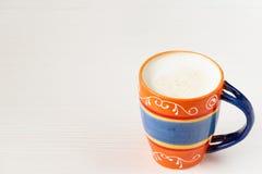 Оранжевая чашка молока и кофе на белой деревянной предпосылке Стоковое Изображение RF