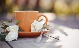 Оранжевая чашка с ложкой и белым dogrose Стоковое Фото