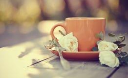 Оранжевая чашка с ложкой и белым dogrose Стоковое Изображение