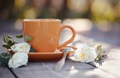 Оранжевая чашка с ложкой и белым dogrose Стоковое Изображение RF