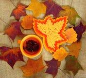 Оранжевая чашка с чаем на предпосылке листьев осени Стоковые Изображения RF