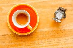 Оранжевая чашка эспрессо с карманным вахтой Стоковое Изображение
