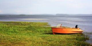 Оранжевая шлюпка на lakeshore ледовитый Лапландии природы русский северно стоковое изображение