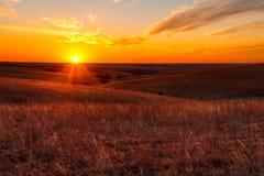 Оранжевое зарево захода солнца в холмах огнива Канзаса Стоковое фото RF