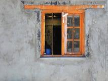 Оранжевое окно на стене цемента серой, деревянных винтажных рамках и пакостном стекле Стоковая Фотография RF