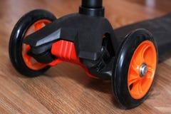 Оранжевое фото самоката трицикла на деревянной предпосылке Стоковые Изображения RF